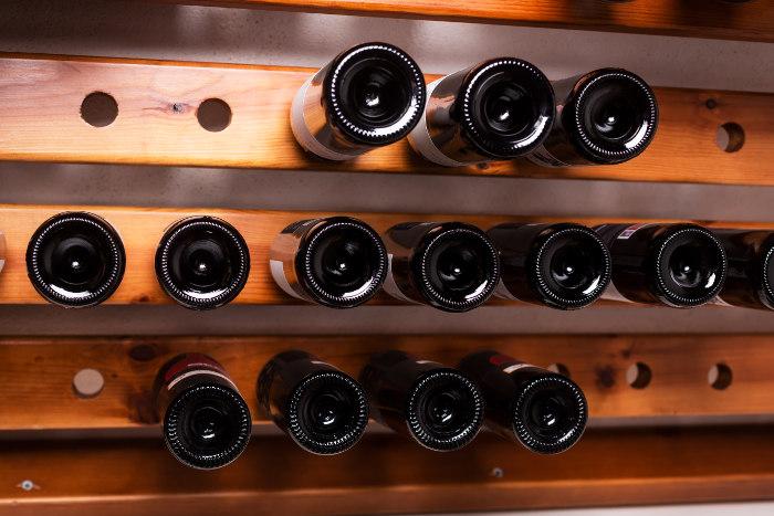 Butelki wina jako inwestycja - na półkach w piwniczce