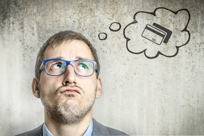 Karta debetowa czy kredytowa - w chmurce - mężczyzna myślący nad wyborem