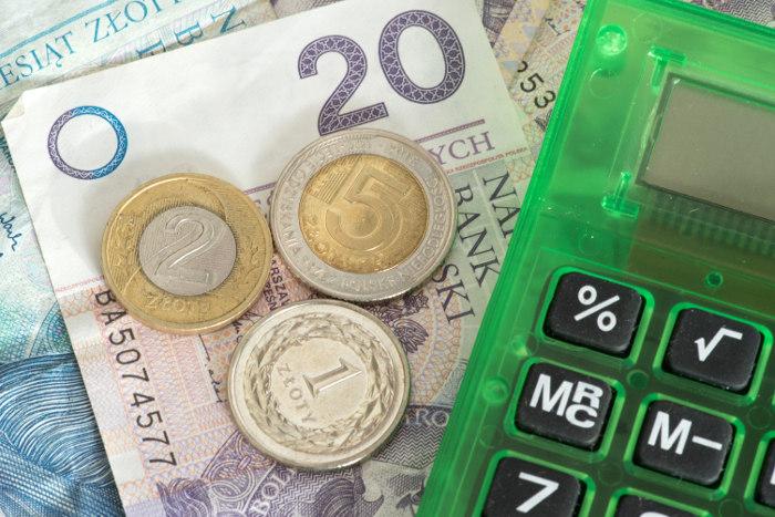 banknoty 50 i 20 złotych oraz monety i kalkulator